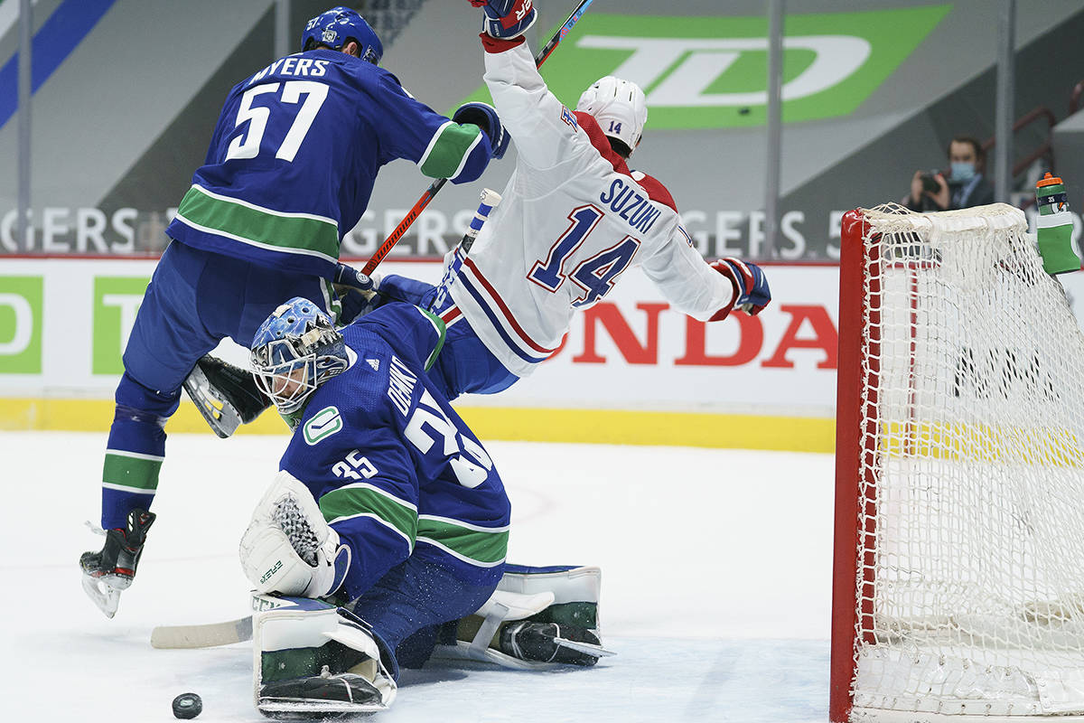 Vancouver Canucks defenceman Tyler Myers (57) clears Montreal Canadiens centre Nick Suzuki (14) away from Canucks goaltender Thatcher Demko (35) during first period NHL action in Vancouver, Thursday, Jan. 21, 2021. THE CANADIAN PRESS/Jonathan Hayward