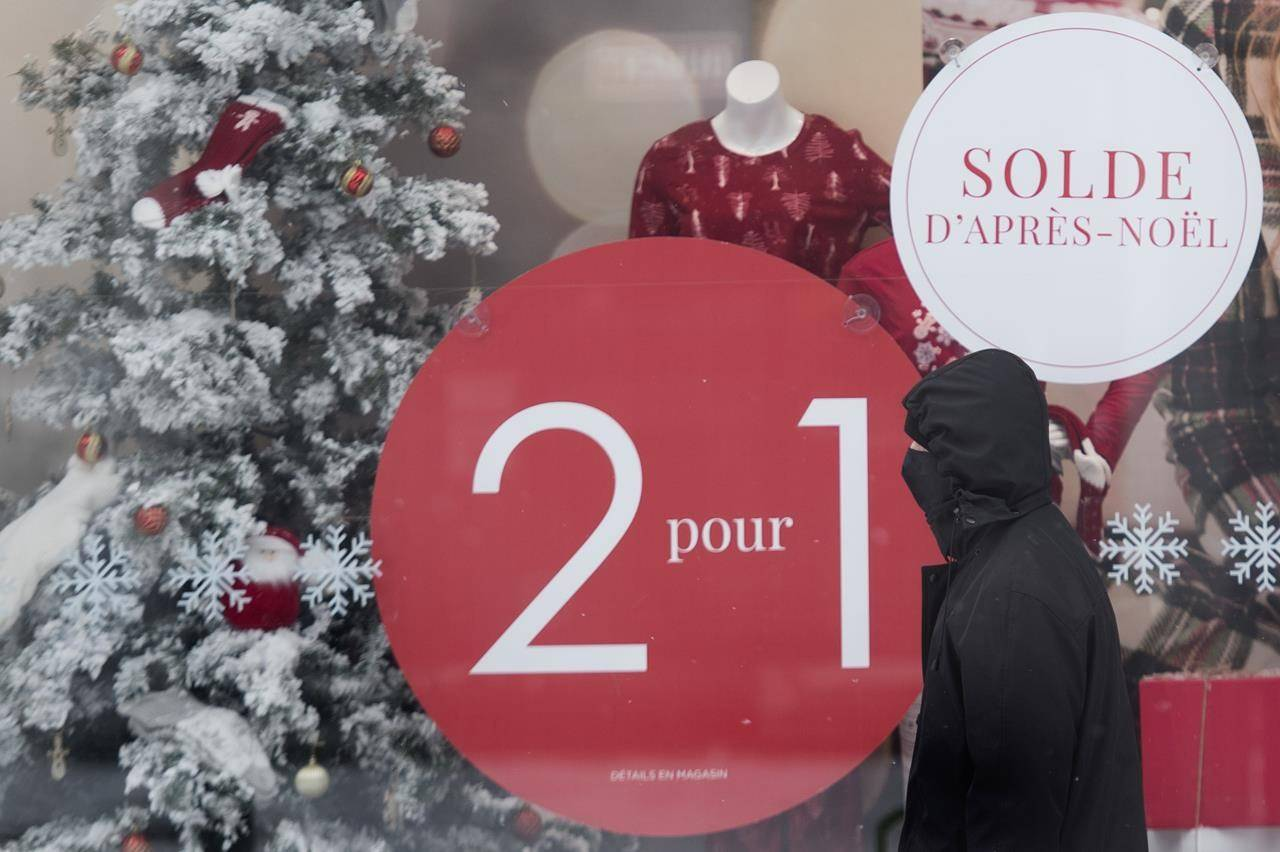 A man wears a face mask as he walks by a storefront window advertising after Christmas sales on Boxing Day in Montreal, Saturday, Dec. 26, 2020. Statistics Canada says retail sales climbed 1.3 per cent to $55.2 billion in November, rising for the seventh straight month. THE CANADIAN PRESS/Graham Hughes