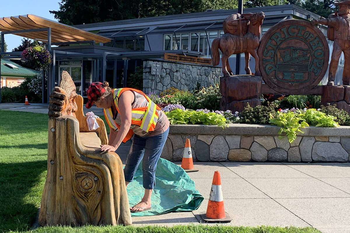 Anne Kosichek was busy sanding and polishing two benches at the front of Hope Memorial Park, in preparation for the 2019 Chainsaw Carving Competition. Kosichek designed the benches, and local chainsaw carver Pete Ryan created them. They were donated two years ago to the District. (Jessica Peters/ Black Press)