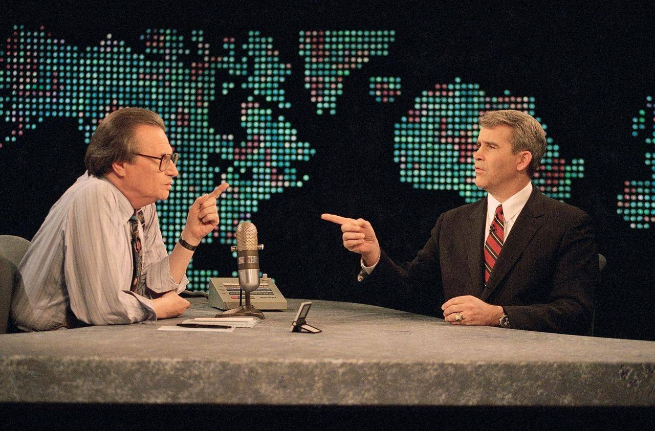 FILE - IN this Jan. 26, 1994 file photo, Oliver North talks to television show host Larry King prior to the start of CNN's 'Larry King Live' in Washington. King, who interviewed presidents, movie stars and ordinary Joes during a half-century in broadcasting, has died at age 87. Ora Media, the studio and network he co-founded, tweeted that King died Saturday, Jan. 23, 2021 morning at Cedars-Sinai Medical Center in Los Angeles. (AP Photo/Shayna Brennan, File)