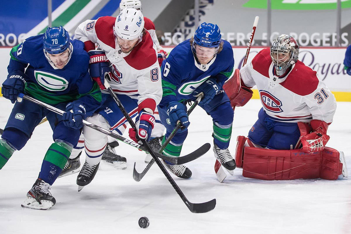 Vancouver Canucks' Tanner Pearson (70) and Brock Boeser (6) vie for the puck against Montreal Canadiens' Ben Chiarot (8) in front of goalie Carey Price (31) during the second period of an NHL hockey game in Vancouver, on Saturday, Jan. 23, 2021. THE CANADIAN PRESS/Darryl Dyck