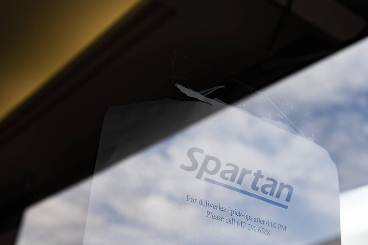 A sign regarding deliveries is seen on a glass door at the offices of Spartan Bioscience, makers of a made-in-Canada, rapid testing device for COVID-19, in Ottawa, on Monday, May 4, 2020. THE CANADIAN PRESS/Justin Tang