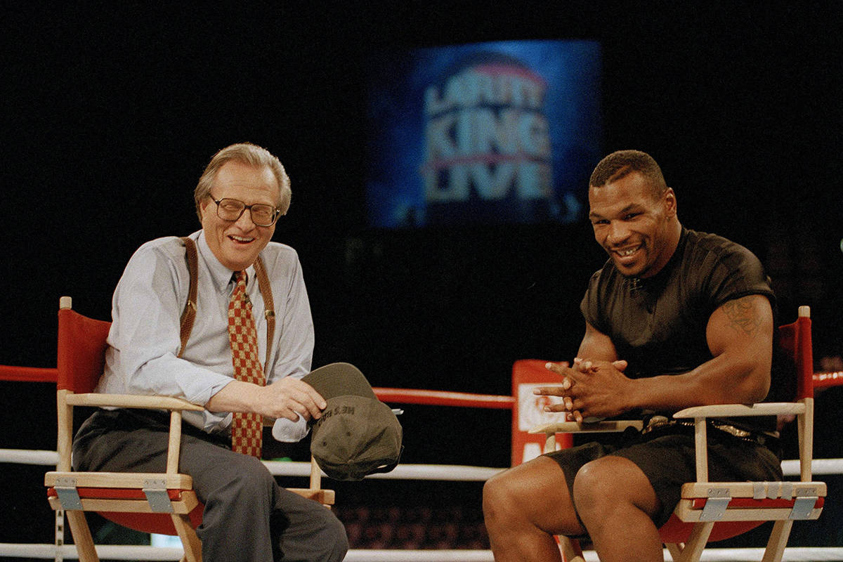 "FILE - In this Aug. 16, 1995 file photo, former heavyweight champion Mike Tyson, right, shares a laugh with TV talk show host Larry King during the broadcasting of the ""Larry King Live"" show from inside the ring at the MGM Grand Gardens in Las Vegas. King, who interviewed presidents, movie stars and ordinary Joes during a half-century in broadcasting, has died at age 87. Ora Media, the studio and network he co-founded, tweeted that King died Saturday, Jan. 23, 2021 morning at Cedars-Sinai Medical Center in Los Angeles. (AP Photo/Lennox McLendon, File)"