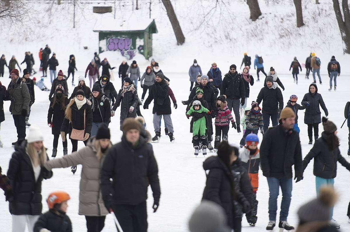 People skate on a lake in a city park in Montreal, Sunday, January 10, 2021. THE CANADIAN PRESS/Graham Hughes