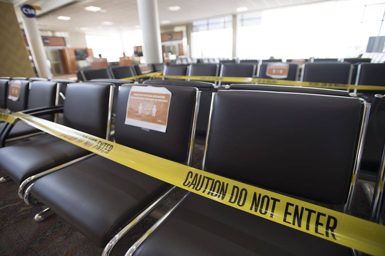 Seats in the waiting area of domestic departures lounge of Calgary International Airport are seen with caution tape on them on June 9, 2020. THE CANADIAN PRESS/Jonathan Hayward