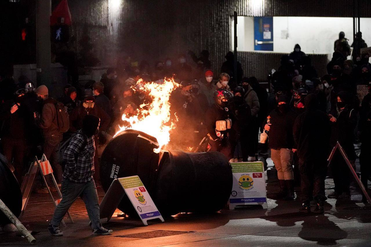 A trash can burns as people take part in a protest against police brutality, late Sunday, Jan. 24, 2021, in downtown Tacoma, Wash., south of Seattle. The protest came a day after at least two people were injured when a Tacoma Police officer responding to a report of a street race drove his car through a crowd of pedestrians that had gathered around him. Several people were knocked to the ground and at least one person was run over. (AP Photo/Ted S. Warren)