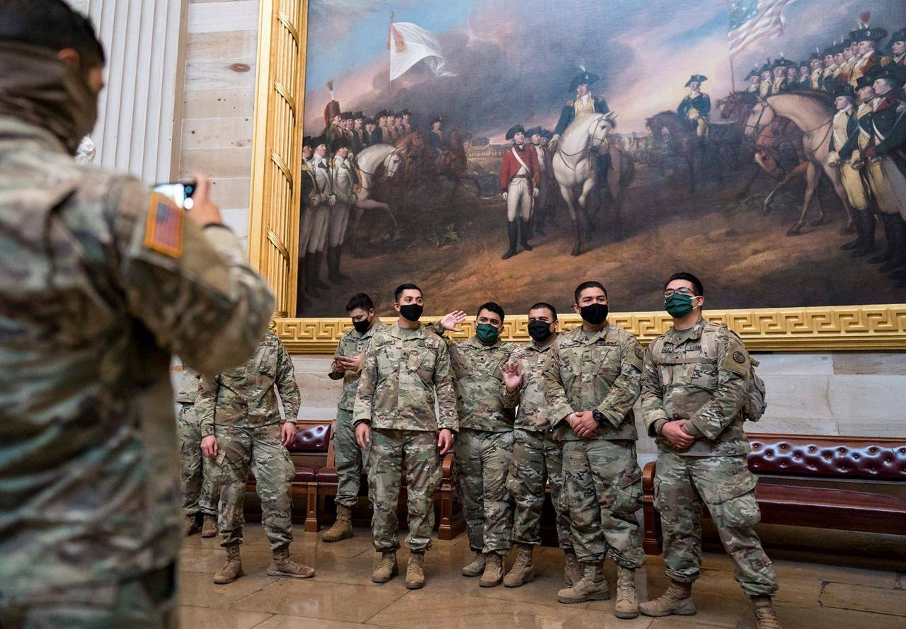 National Guard troops tour the Rotunda at the U.S. Capitol in Washington, during a break from reinforcing security, Monday, Jan. 25, 2021. They are posing for souvenir photos beneath the famous painting, Surrender of Lord Cornwallis. (AP Photo/J. Scott Applewhite)