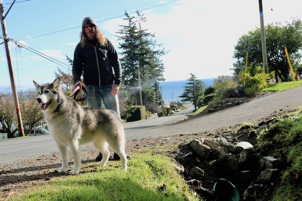 Marc Porpaczy said he's glad he delayed his daily walk with his dog, Juno, after a car crashed just outside his driveway just before 8 p.m. on Tuesday, Jan. 25. (Aaron Guillen/News Staff)