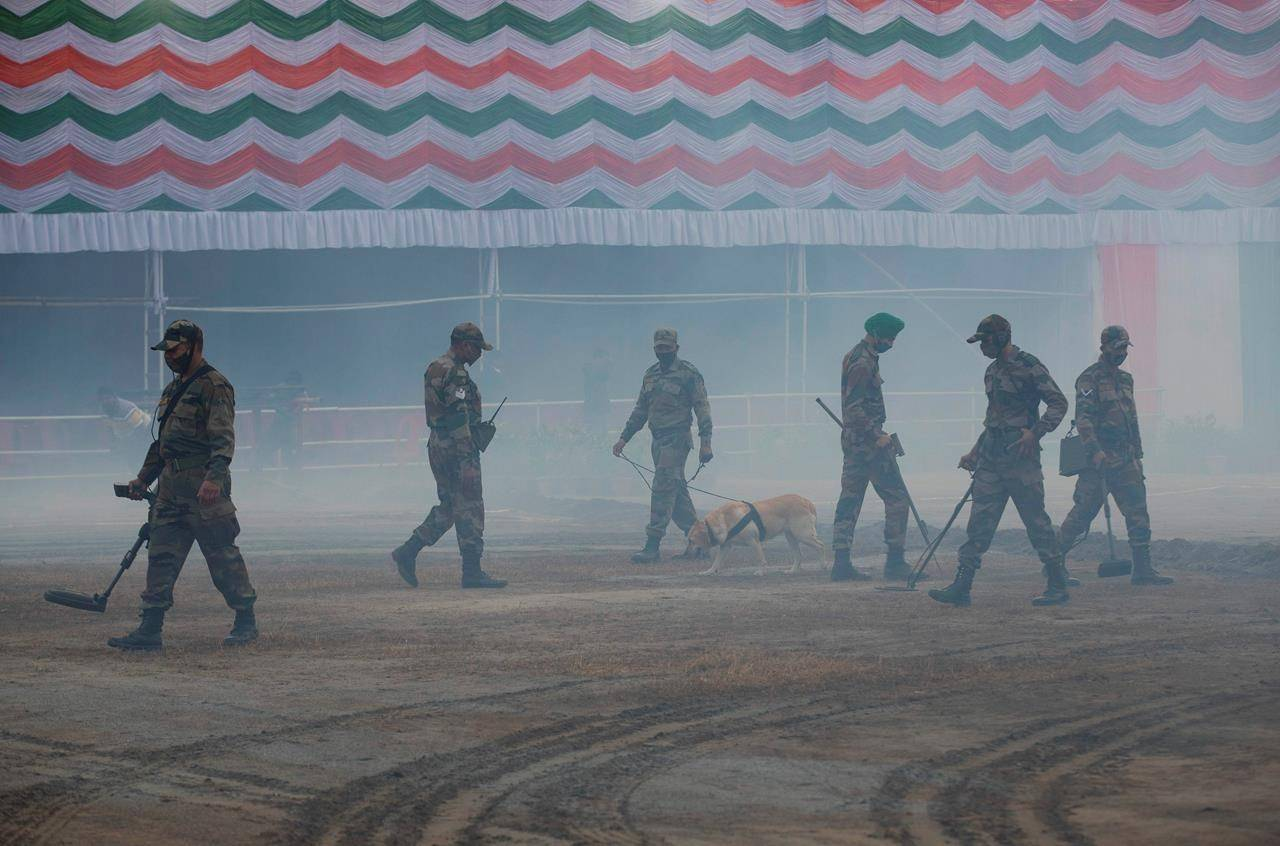 Indian army soldiers with a sniffer dog perform security checks at a venue of Indian Republic Day ceremonial parade in Gauhati, India, Monday, Jan. 25, 2021. Republic Day marks the anniversary of the adoption of the India's constitution on Jan. 26, 1950. (AP Photo/Anupam Nath)