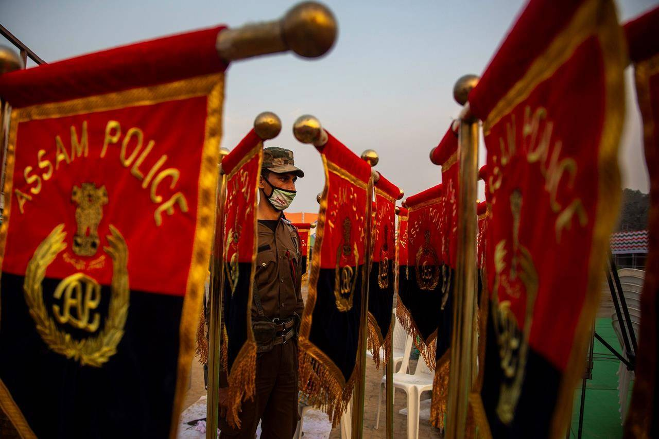 An Assam police person looks on as a worker, unseen, prepares the stands with flags at a venue of Indian Republic Day ceremonial parade in Gauhati, India, Monday, Jan. 25, 2021. Republic Day marks the anniversary of the adoption of the India's constitution on Jan. 26, 1950. (AP Photo/Anupam Nath)