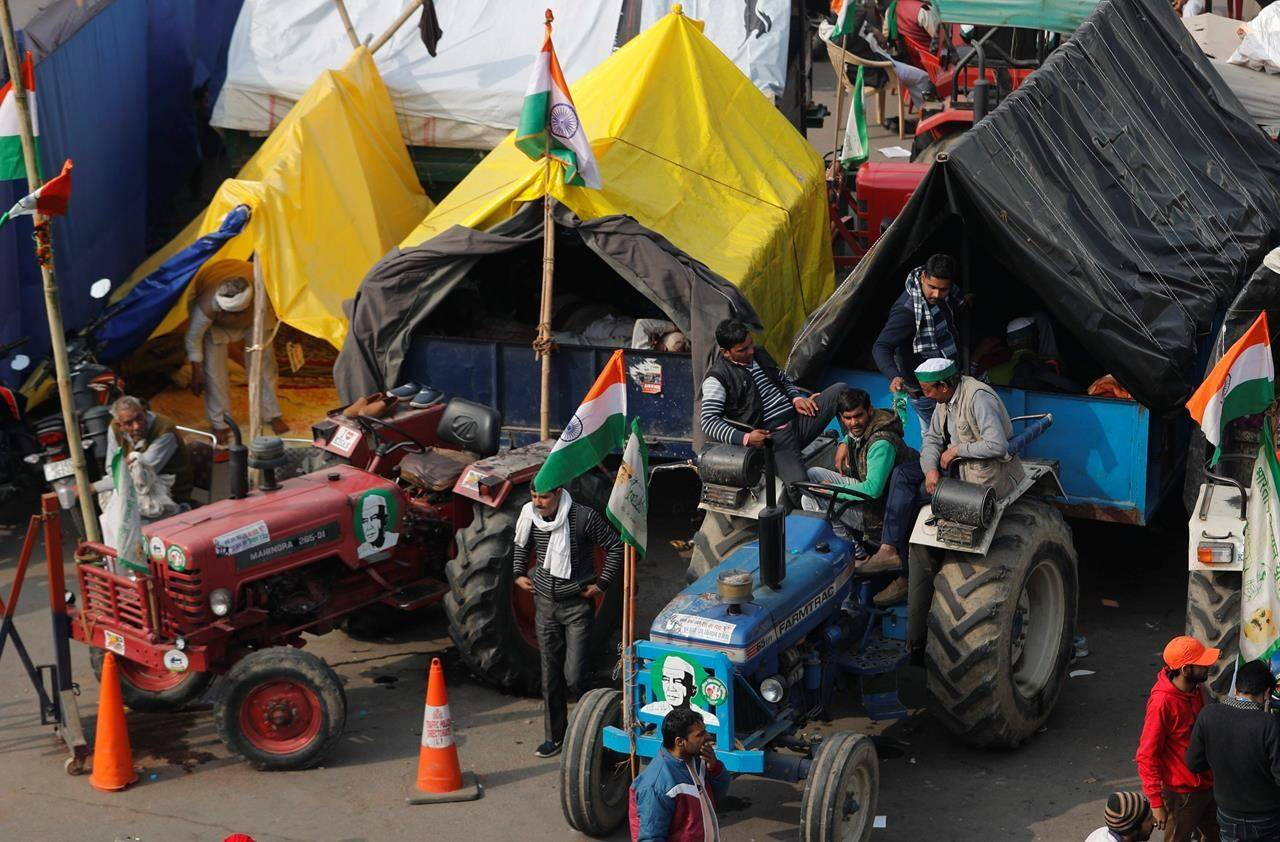 Indian farmers sit on their tractor after arriving at the Delhi-Uttar Pradesh border for Tuesday's tractor rally in New Delhi, India, Monday, Jan. 25, 2021. Thousands of farmers gathered on the borders of Delhi for a massive tractor rally on Tuesday against the three contentious farm laws when India will celebrate its Republic day with a military and cultural parade. The two-month-old old blockade of highways connecting the capital with the country's north continues as the talks have remained deadlocked with the government refusing to scrap the new agricultural reform laws which the farmers say will benefit large corporations. (AP Photo/Manish Swarup)
