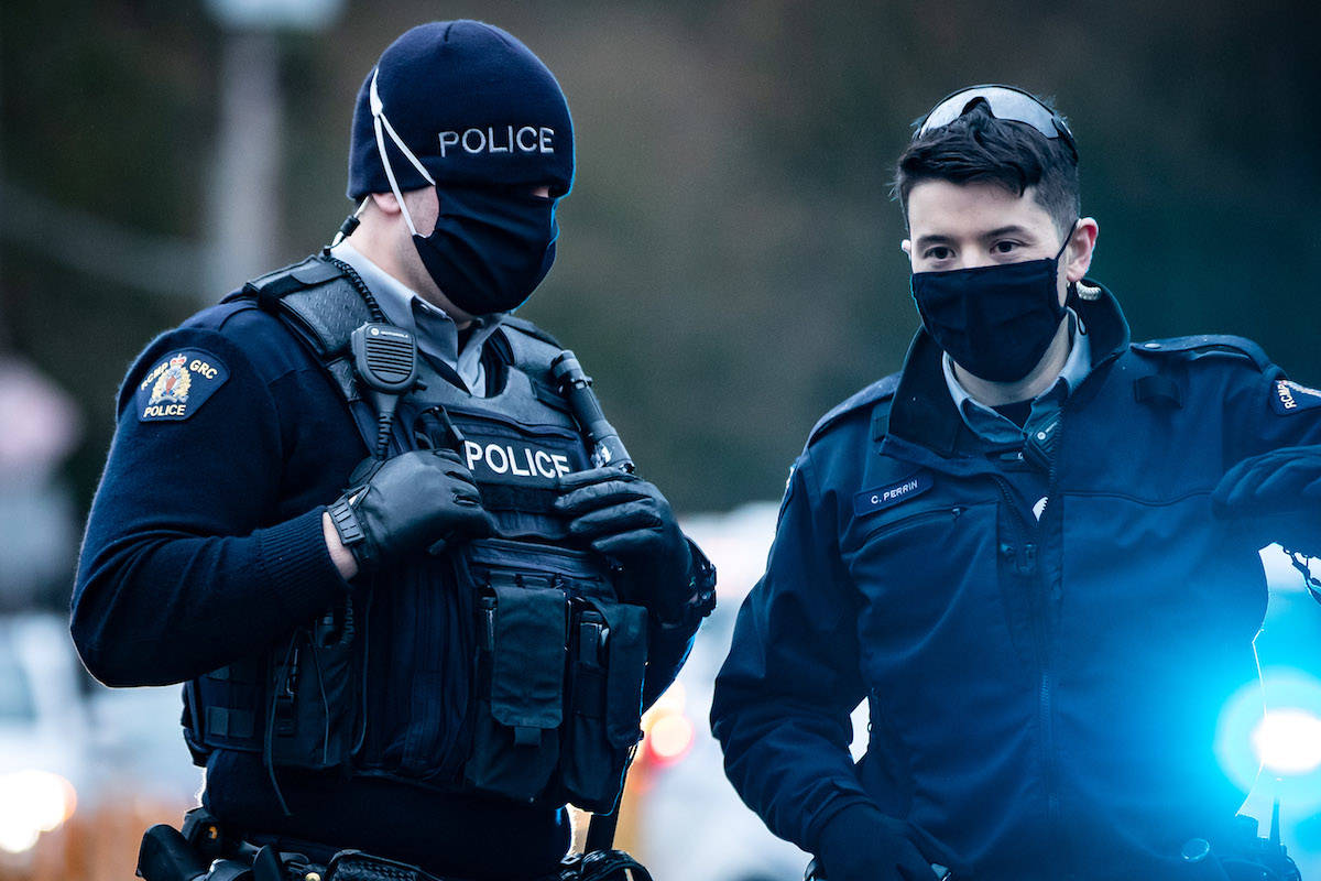 RCMP officers wearing face masks to curb the spread of COVID-19 stand by. (THE CANADIAN PRESS/Darryl Dyck)