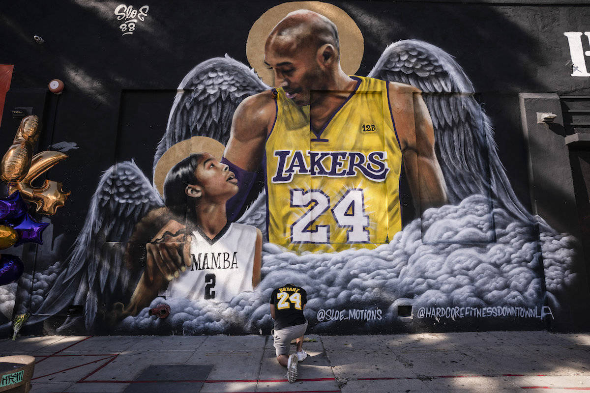 Adam Dergazarian, bottom center, pays his respect for Kobe Bryant and his daughter, Gianna, in front of a mural painted by artist Louie Sloe Palsino, Tuesday, Jan. 26, 2021, in Los Angeles. (AP Photo/Jae C. Hong)