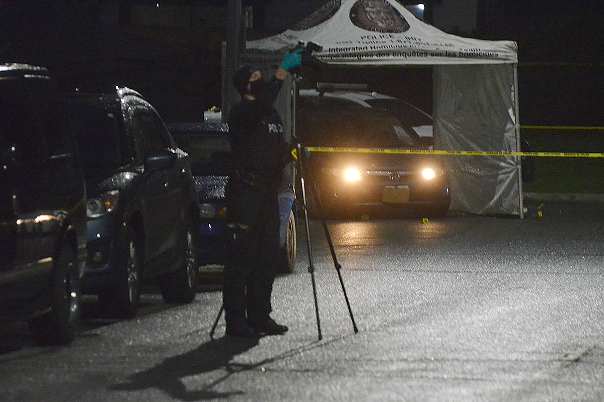 An investigator sets up a camera near a vehicle under investigation by IHIT at a murder scene in Langley City Wednesday morning. (Matthew Claxton/Langley Advance Times)