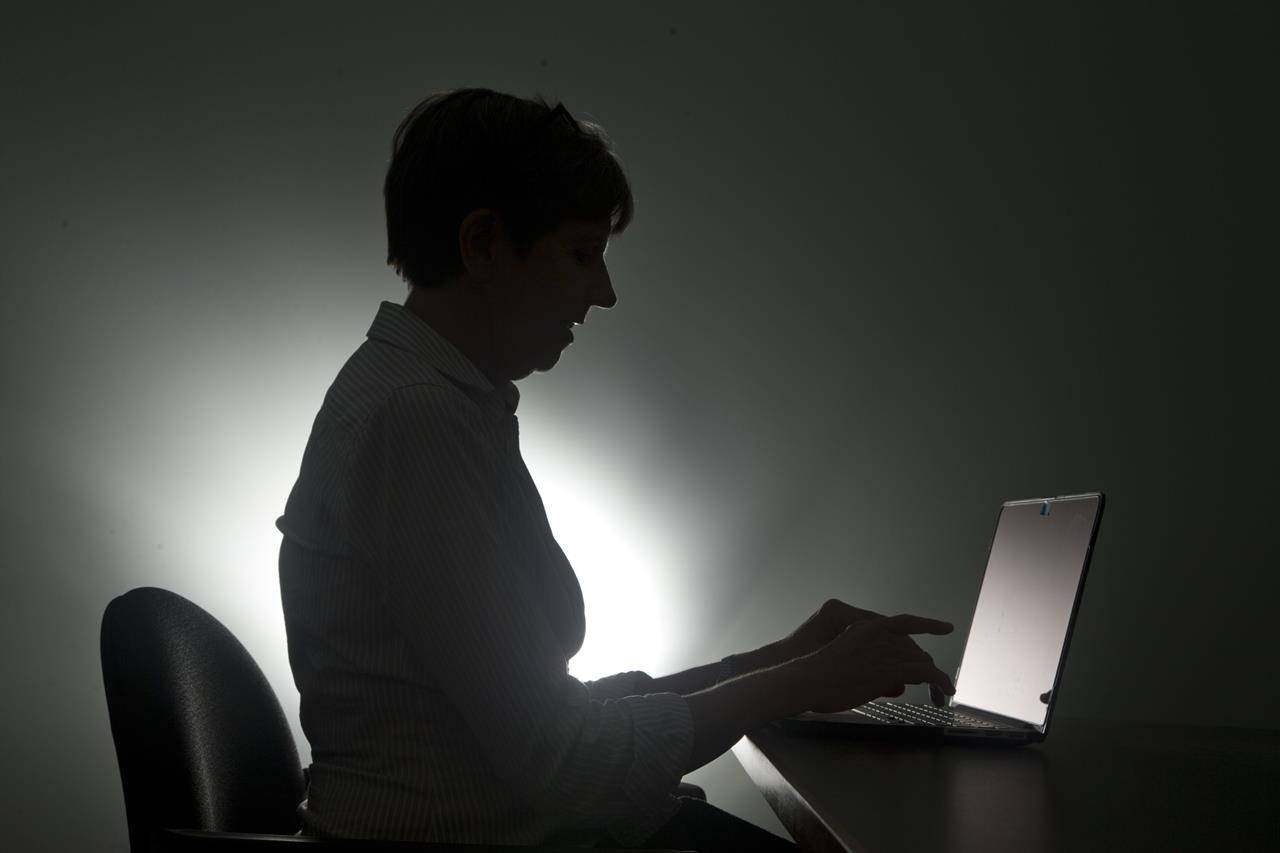 A woman types on her laptop in Miami in a Monday, Dec. 12, 2016, photo illustration. An investigation into a scourge of NetWalker ransomware attacks has led to the arrest of a Canadian man, the U.S. Department of Justice said on Wednesday. According to an indictment, police in Florida charged Sebastien Vachon-Desjardins of Gatineau, Que., with illegally obtaining more than $27.6 million. THE CANADIAN PRESS/AP/Wilfredo Lee