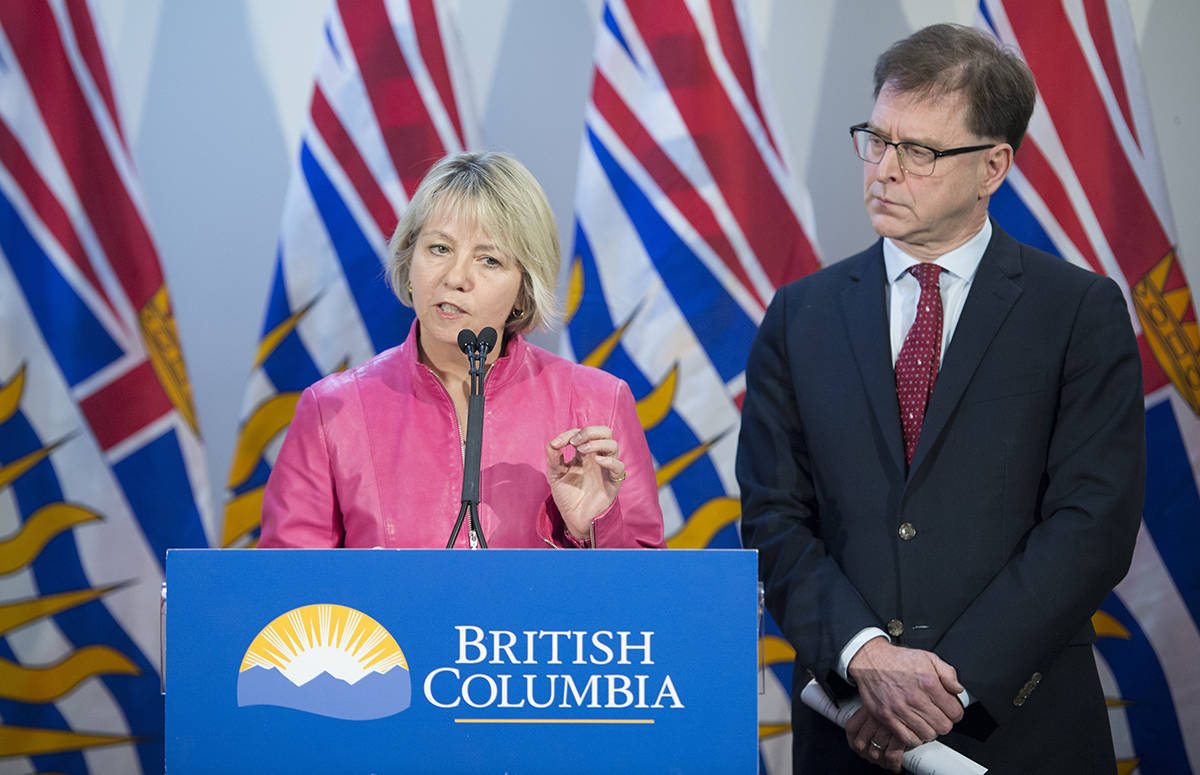 British Columbia Health Minister Adrian Dix looks on as Provincial Health Officer Dr. Bonnie Henry addresses the media during a news conference at the BC Centre of Disease Control in Vancouver B.C. (THE CANADIAN PRESS/Jonathan Hayward)