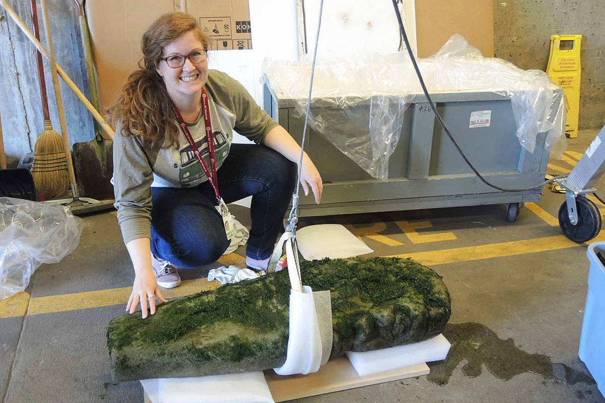 Royal B.C. Museum conservator Megan Doxsey-Whitfield kneels next to a carved stone pillar believed to have significance as a First Nations cultural marker by local Indigenous people. The pillar was discovered on the beach at Dallas Road earlier this month. Museum curatorial staff are working with Songhees and Esquimalt Nation representatives to gain a clearer picture of its use. (Photo courtesy Royal BC Museum)