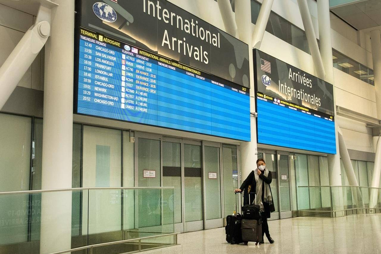 A lone passenger stands outside the International Arrivals area at Pearson Airport in Toronto on Tuesday, Jan. 26, 2021. As the federal government prepares to slap new restrictions on foreign arrivals, Health Canada data suggest a growing number of infections directly connected to international travel. THE CANADIAN PRESS/Frank Gunn