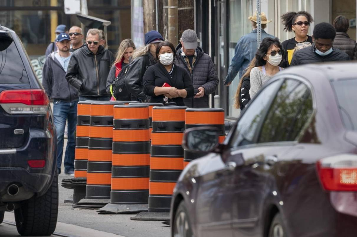 Pedestrian walk outside a grocery store in Toronto on Sunday, May 17, 2020. A new report says Black Canadians and people from most other minority groups tend to disproportionately lose out on federal civil service jobs they apply for compared with other Canadians.THE CANADIAN PRESS/Frank Gunn