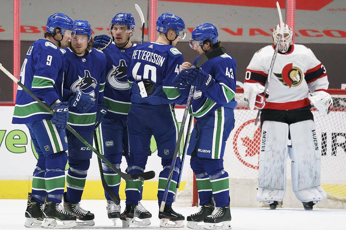Ottawa Senators goaltender Matt Murray (30) looks on as Vancouver Canucks right wing Brock Boeser (6) celebrates his goal with teammates during first period NHL action in Vancouver, Thursday, Jan. 28, 2021. THE CANADIAN PRESS/Jonathan Hayward