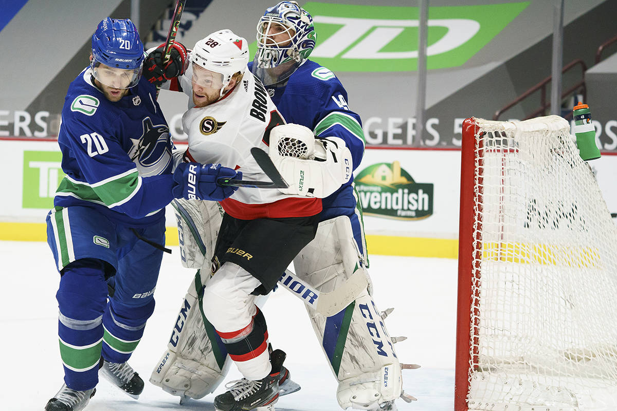 Vancouver Canucks centre Brandon Sutter (20) tries to clear Ottawa Senators right wing Connor Brown (28) from in front of Vancouver Canucks goaltender Braden Holtby (49) during first period NHL action in Vancouver, Thursday, Jan. 28, 2021. THE CANADIAN PRESS/Jonathan Hayward