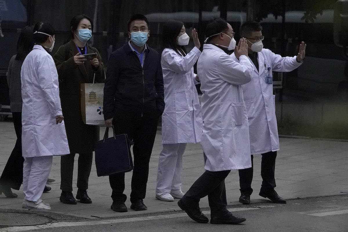 Chinese medical staff wave farewell to a World Health Organization team during their visit to Hubei Province Xinhua Hospital in Wuhan in central China on Friday, Jan. 29, 2021. The WHO team visited the hospital where China says the first COVID-19 patients were treated more than a year ago as part of the experts' long-awaited fact-finding mission on the origins of the coronavirus. (AP Photo/Ng Han Guan)