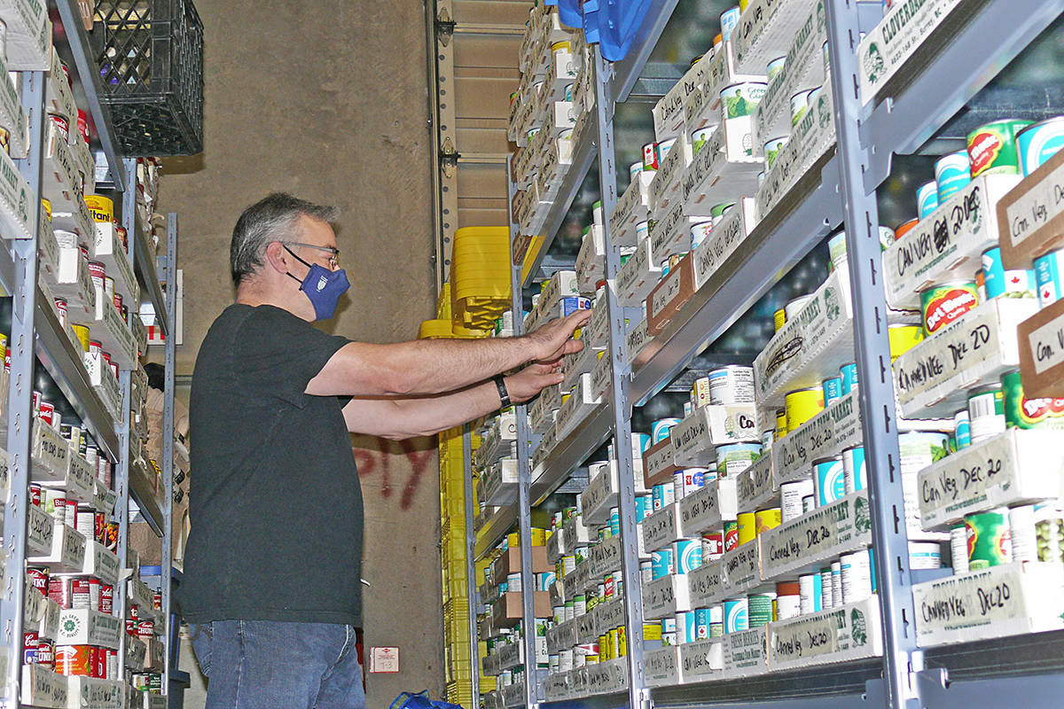 Volunteer Andrew Penny was sorting supplies at the Source Langley Food Bank on Dec. 21. The food bank is about to launch a delivery service and is hoping to find a location for Aldergrove distribution. (Dan Ferguson/Langley Advance Times)