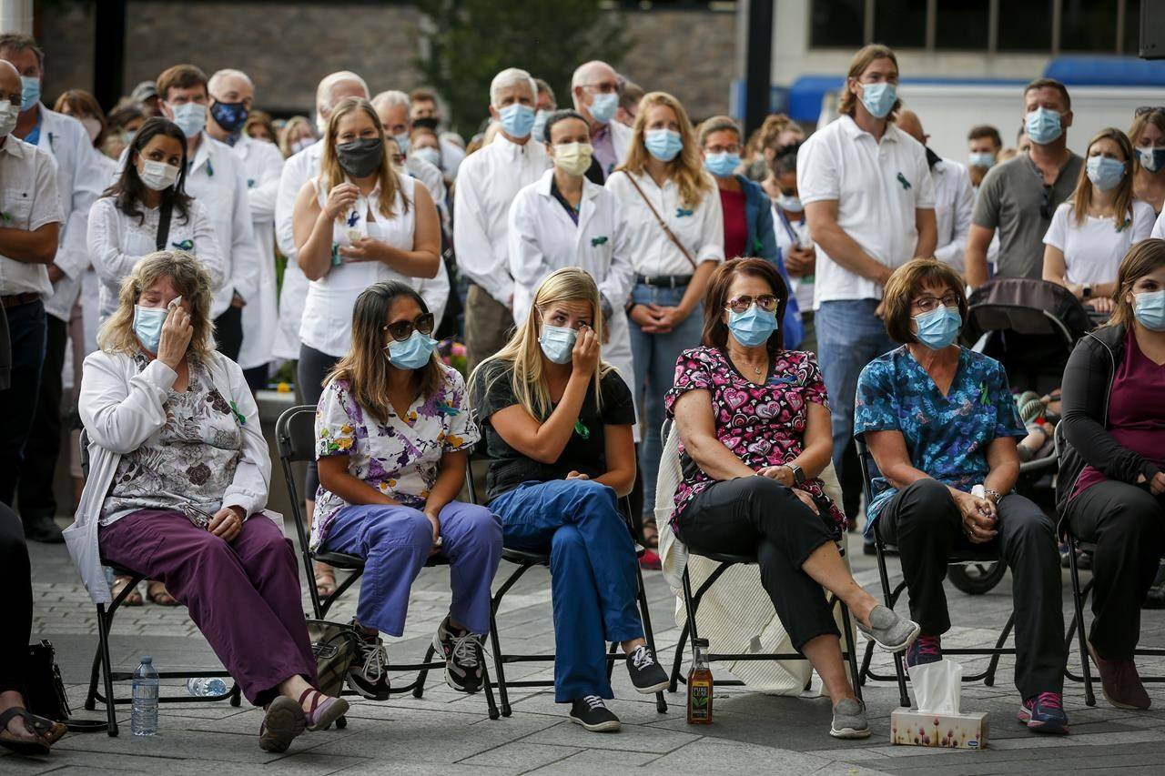 Village Mall Walk-in-clinic employees, front row, and health-care workers attend a vigil for Dr. Walter Reynolds who was killed at a walk-in clinic earlier this week, in Red Deer, Alta., Friday, Aug. 14, 2020. THE CANADIAN PRESS/Jeff McIntosh