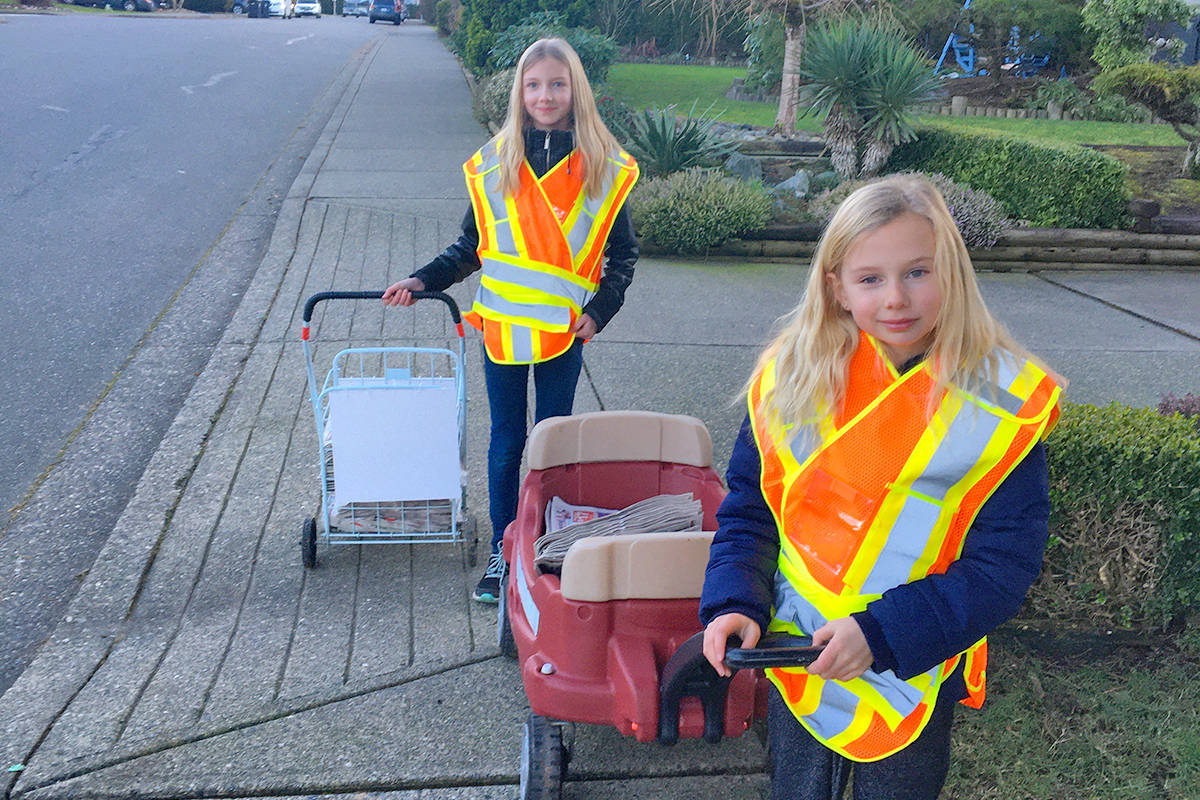 Sisters Zoey, 12, and nine-year-old Lena Jacobi are only a few weeks into their first-ever job as newspaper carriers for the Langley Advance Times. The pair are working to save some money to purchase books, says Mom. (Special to Langley Advance Times).