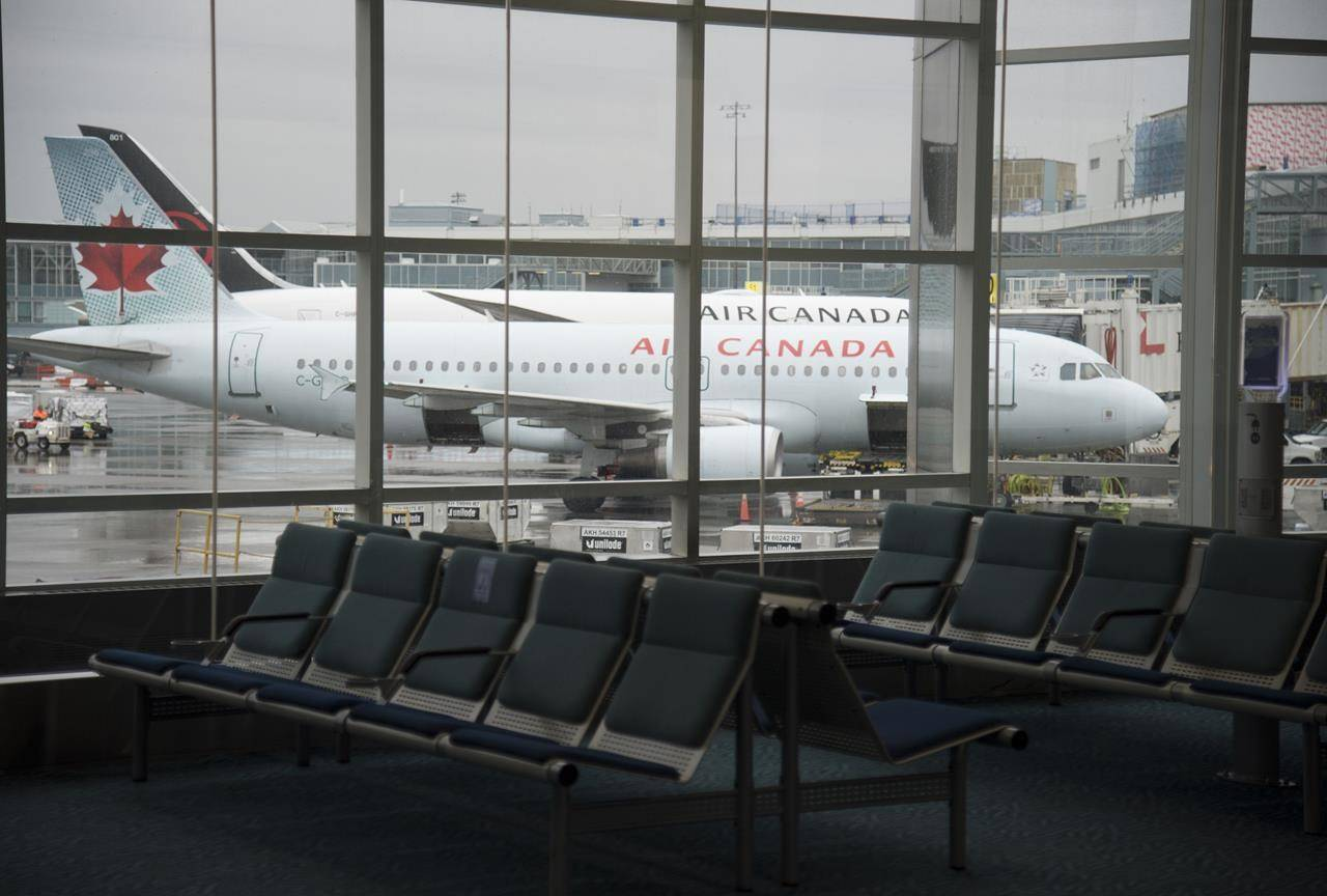 A plane is seen through the window on the tarmac of Vancouver International Airport as the waiting room is empty Tuesday, June 9, 2020. THE CANADIAN PRESS/Jonathan Hayward
