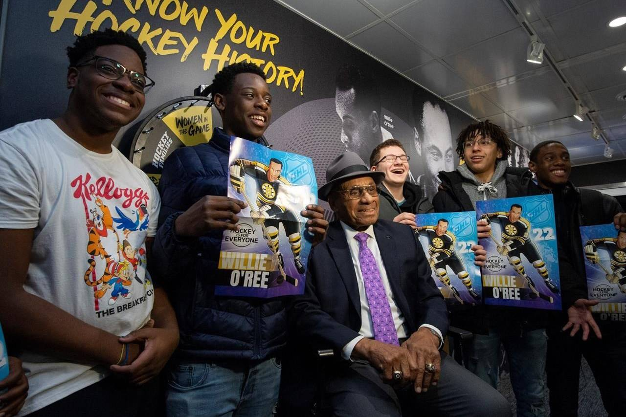 Willie O'Ree, the first black player in the NHL and member of the Hockey Hall of Fame, sits for a photo with students from St. Peter's High School in the NHL's Black Hockey History Mobile Museum, an initiative for Black History Month, in Ottawa, on February 3, 2020. THE CANADIAN PRESS/Justin Tang