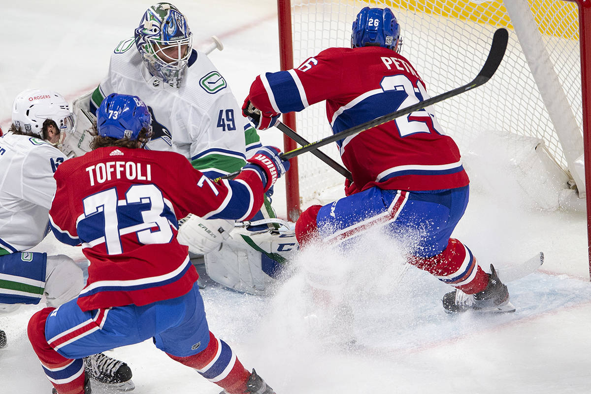 Montreal Canadiens defenceman Jeff Petry (26) scores his second goal of the game against Vancouver Canucks goaltender Braden Holtby (49) as teammate Canadiens right wing Tyler Toffoli (73) looks on during second period NHL hockey action Monday, Feb. 1, 2021 in Montreal. THE CANADIAN PRESS/Ryan Remiorz