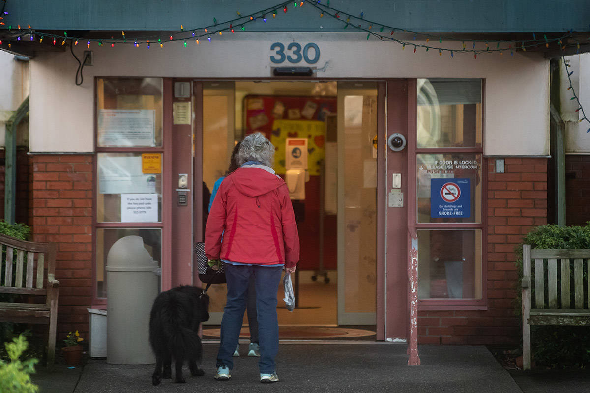 People wait to be screened before entering Little Mountain Place, a long-term care home that has had 38 residents die since a COVID-19 outbreak was declared at the facility in November in Vancouver on Sunday, January 3, 2021. THE CANADIAN PRESS/Darryl Dyck