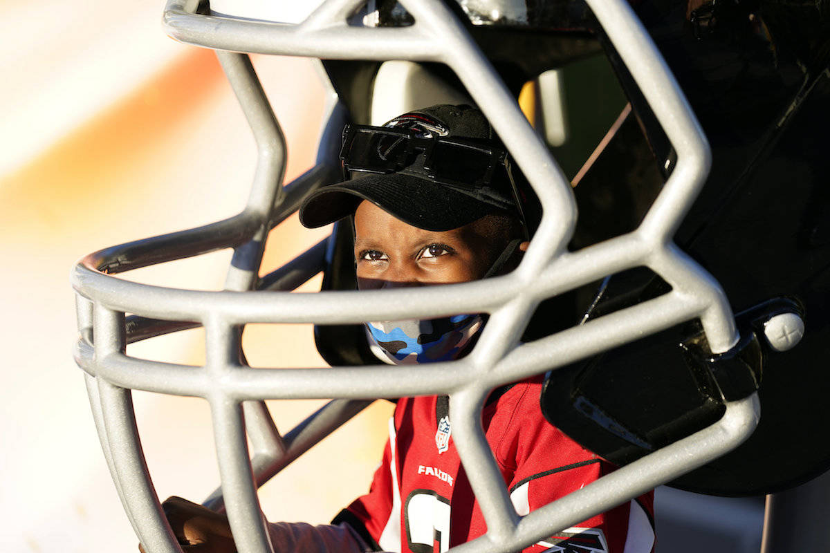 Isaiah Sheppard, 7, sits inside an oversized football helmet at the NFL Experience for Super Bowl LV Friday, Jan. 29, 2021, in Tampa, Fla. Tampa Bay Buccaneers host defending champion Kansas City Chiefs on Sunday. (AP Photo/David J. Phillip)