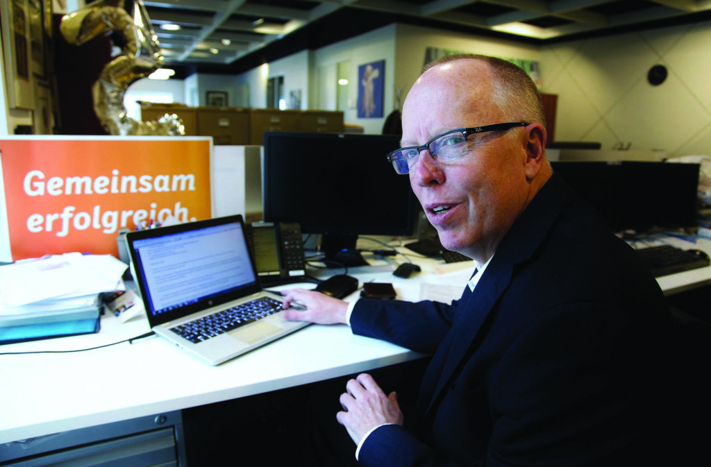 """John Hinds, CEO of News Media Canada (formerly Newspapers Canada) reads an email from PayPal at his office in Toronto on Friday, Feb. 10, 2017. Hinds called it """"scary"""" after PayPal froze his organization's payments account over a weekly newspaper story about a Syrian refugee family in Manitoba. THE CANADIAN PRESS/Colin Perkel"""