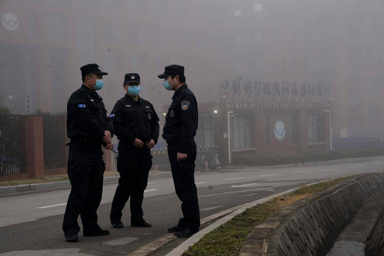Security personnel stand guard near the Wuhan Institute of Virology after a World Health Organization team arrived for a field visit in Wuhan in China's Hubei province Wednesday, Feb. 3, 2021. The WHO team is investigating the origins of the coronavirus pandemic has visited two disease control centers in the province. (AP Photo/Ng Han Guan)
