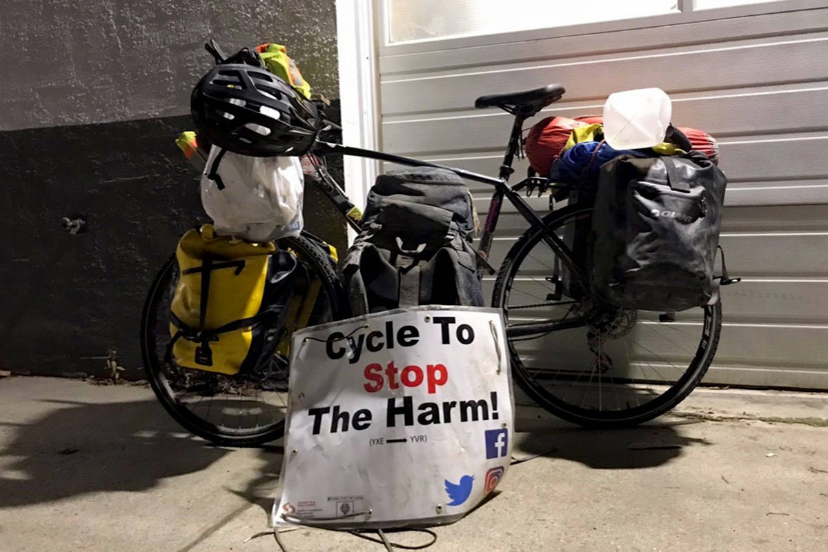 Iliajah Pidskalny's bike is adorned with a sign advertising his cause. He has raised $21,000 for Canadian Drug Policy Coalition and Moms Stop the Harm. (Photo/Iliajah Pidskalny)