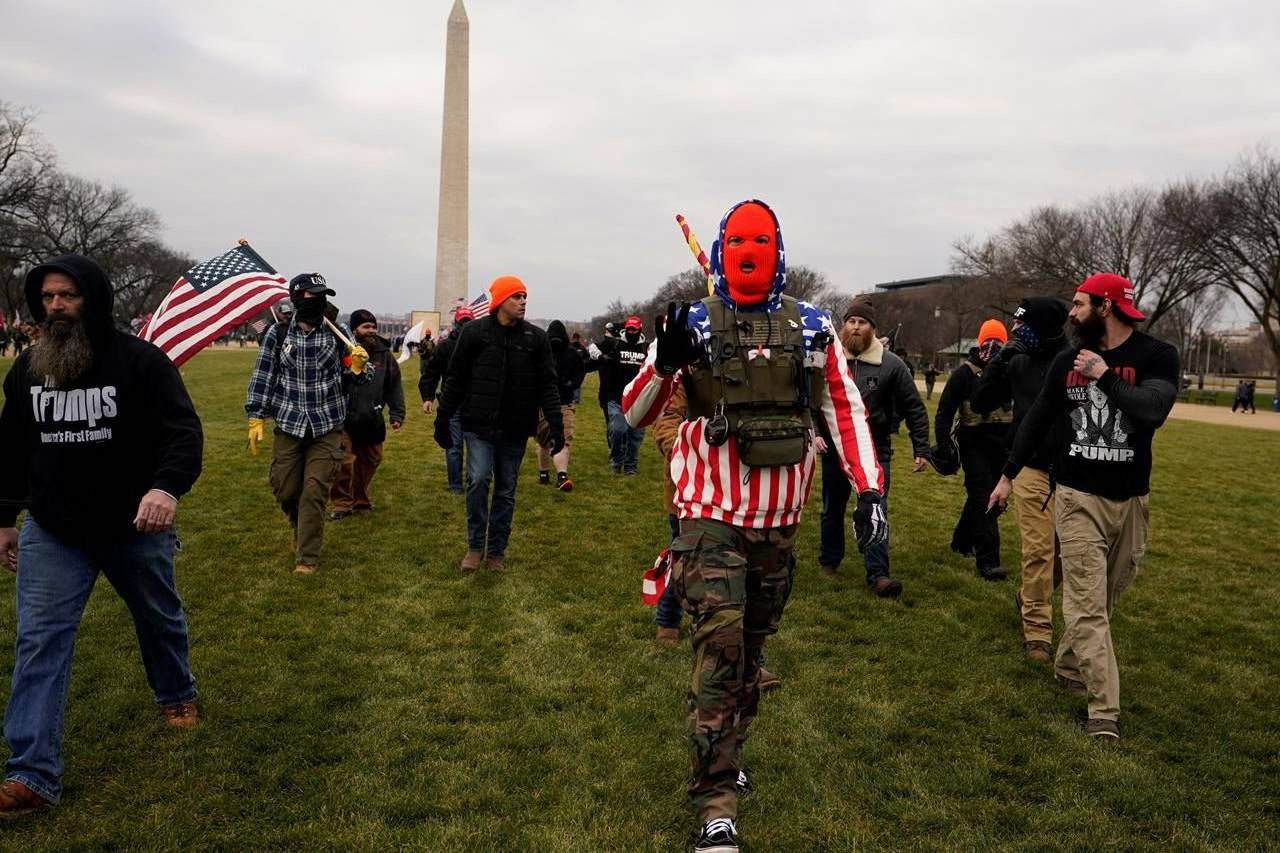 In this Jan. 6, 2021, file photo, people march with those who say they are members of the Proud Boys as they attend a rally in Washington in support of President Donald Trump. THE CANADIAN PRESS/AP/Carolyn Kaster,