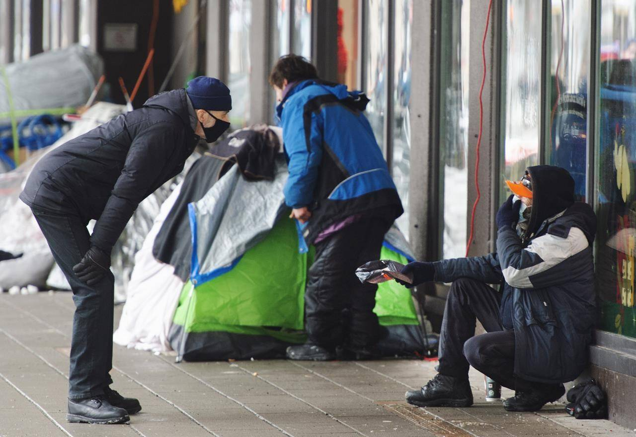 A man chats with a homeless person at a small tent city on Ste-Catherine Street on Jan. 27, 2021, in downtown Montreal. THE CANADIAN PRESS/Ryan Remiorz