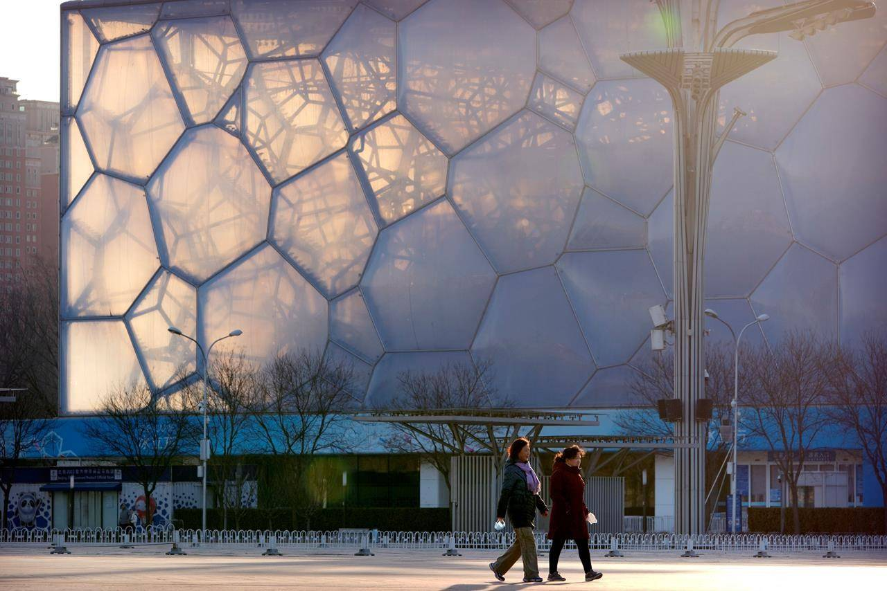 People walk past the Water Cube, which will be known as the Ice Cube when it hosts events for the 2022 Beijing Winter Olympics, in Beijing, Tuesday, Feb. 2, 2021. Canada will not boycott the 2022 Winter Games in Beijing despite calls from human rights organizations to do so. THE CANADIAN PRESS/AP/Mark Schiefelbein