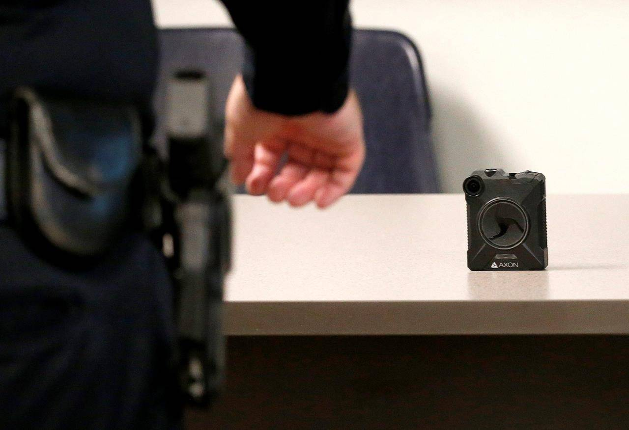 A Phoenix Police Department officer reaches for a new Axon Body 2 body camera as another precinct gets their cameras assigned to them Wednesday, July 3, 2019, in Phoenix. Outfitting RCMP officers with body-worn cameras at 700 detachments will cost an estimated $131 million over five years.THE CANADIAN PRESS/AP/Ross D. Franklin