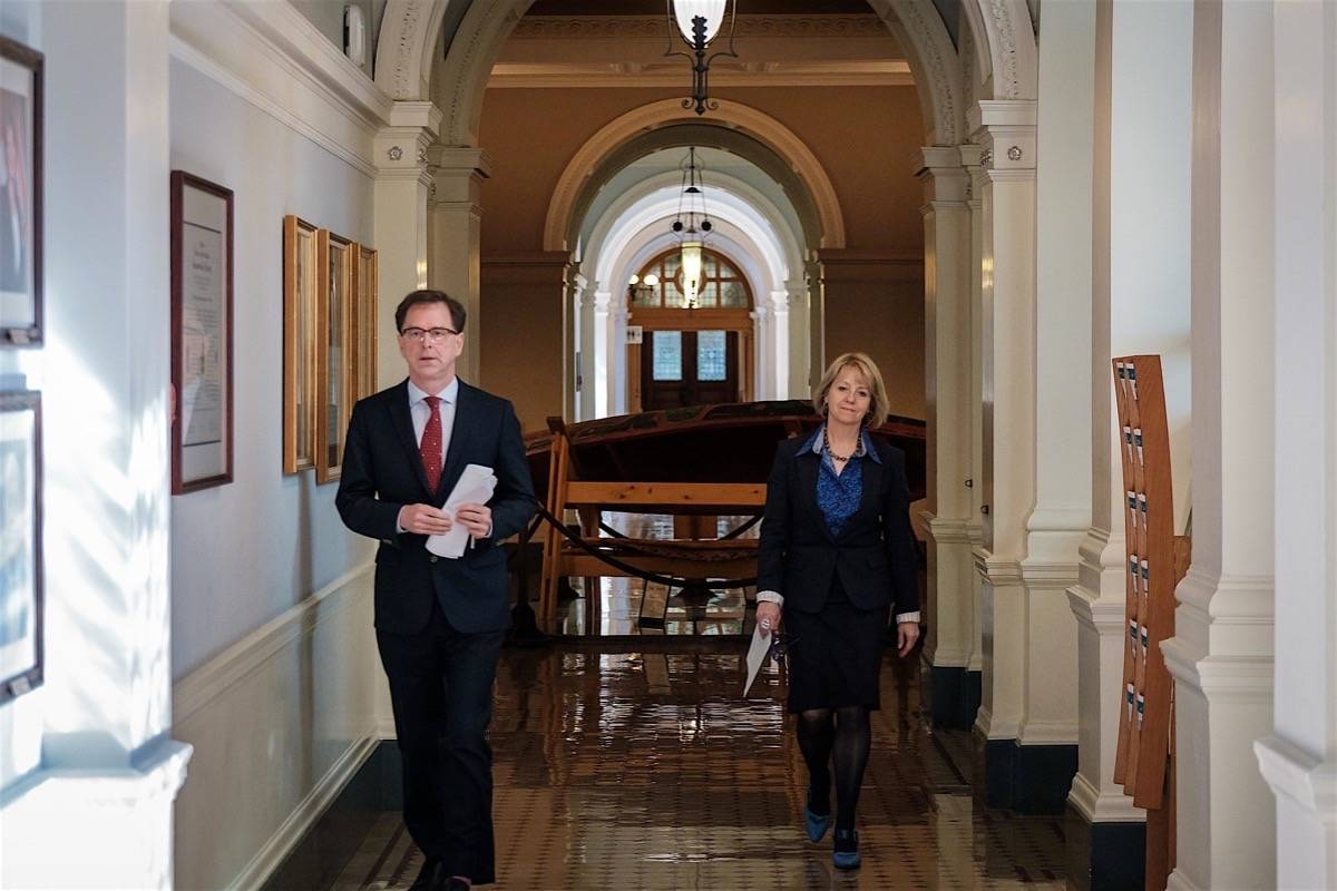 B.C. Health Minister Adrian Dix and provincial health officer Dr. Bonnie Henry head to their daily update on the COVID-19 pandemic, B.C. legislature, April 15, 2020. B.C. has been dealing with the pandemic for a year. (B.C. government)