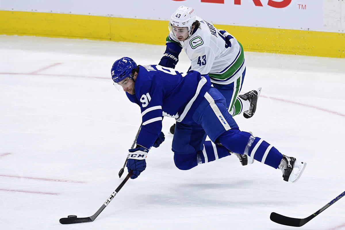 Vancouver Canucks defenceman Quinn Hughes (43) picks up a tripping penalty on Toronto Maple Leafs centre John Tavares (91) during first period NHL action in Toronto on Thursday, Feb. 4, 2021. THE CANADIAN PRESS/Frank Gunn