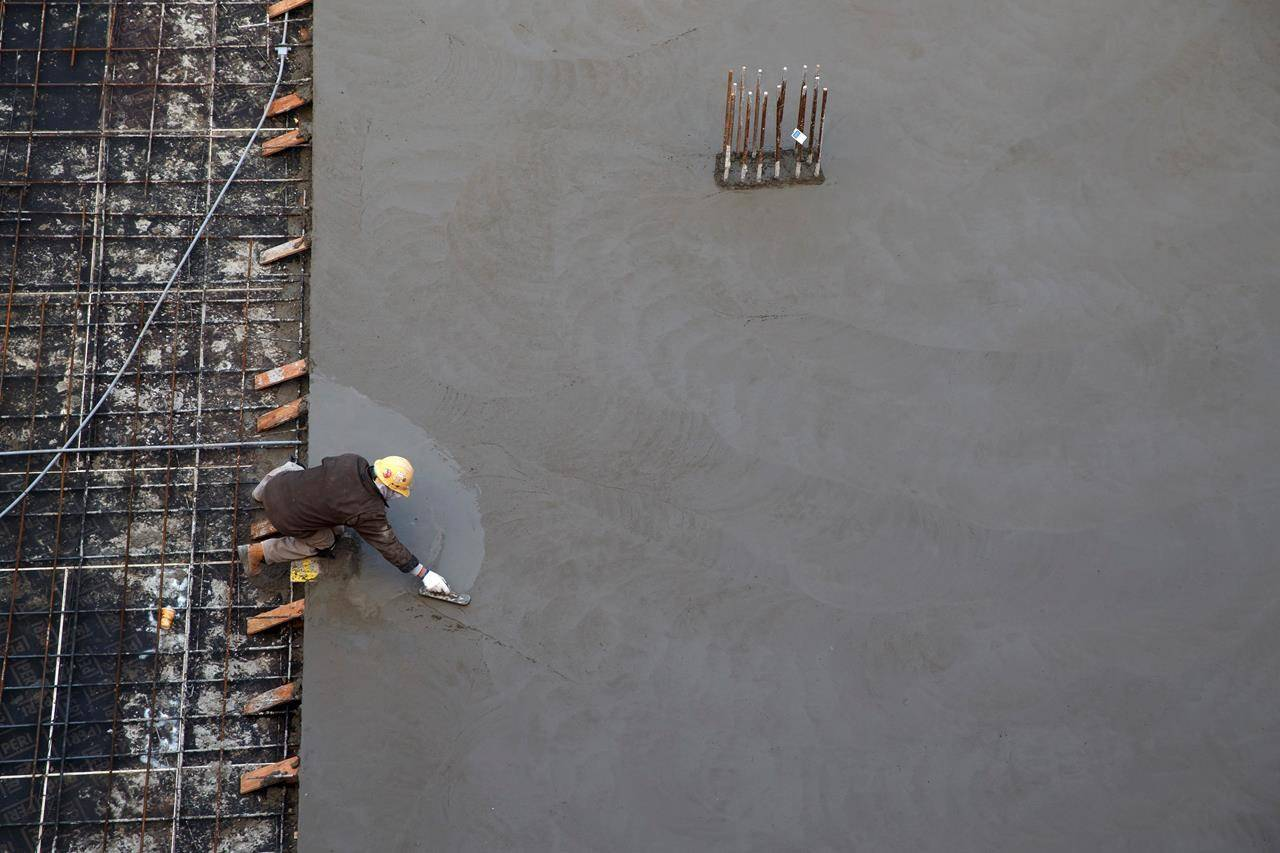 A worker smooths concrete at a housing development in Toronto, Thursday, Jan. 16, 2020. THE CANADIAN PRESS/Cole Burston