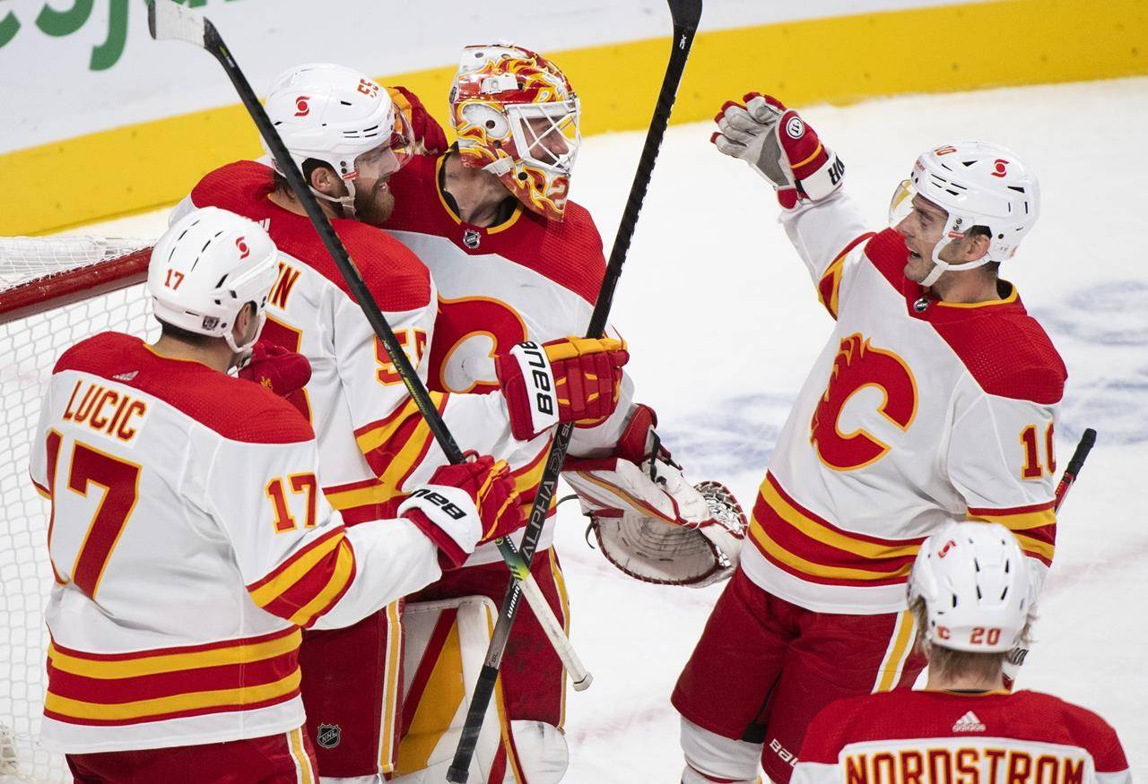 Calgary Flames goaltender Jacob Markstrom celebrates with teammates after defeating the Montreal Canadiens in an NHL hockey game in Montreal, Saturday, January 30, 2021. Markstrom's routine is pretty simple in the NHL's COVID-19 era, but the same can't be said for players south of the border. THE CANADIAN PRESS/Graham Hughes