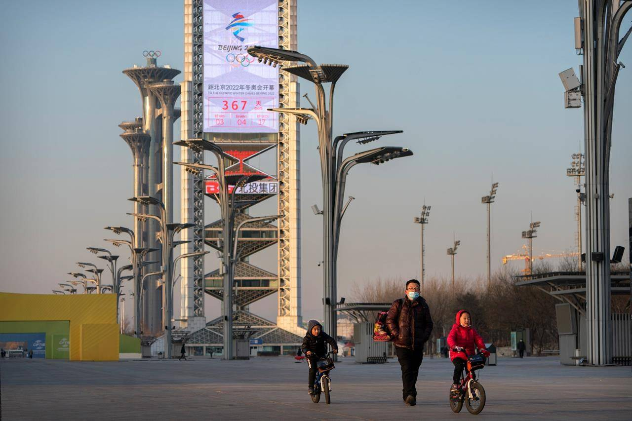 People walk on the Olympic Green near a countdown clock showing slightly more than 1 year to go for the 2022 Beijing Olympics in Beijing, on February 2, 2021. THE CANADIAN PRESS/AP, Mark Schiefelbein