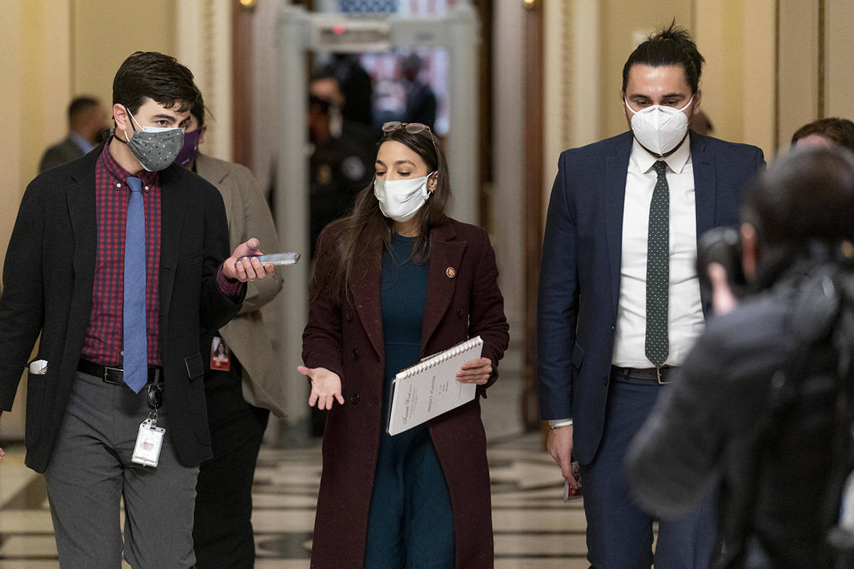 Rep. Alexandria Ocasio-Cortez, D-N.Y., leaves the House floor during a vote to remove Rep. Marjorie Taylor Greene, R-Ga., from committee assignments over her extremist views, on Capitol Hill in Washington, Thursday, Feb. 4, 2021. (AP Photo/Andrew Harnik)