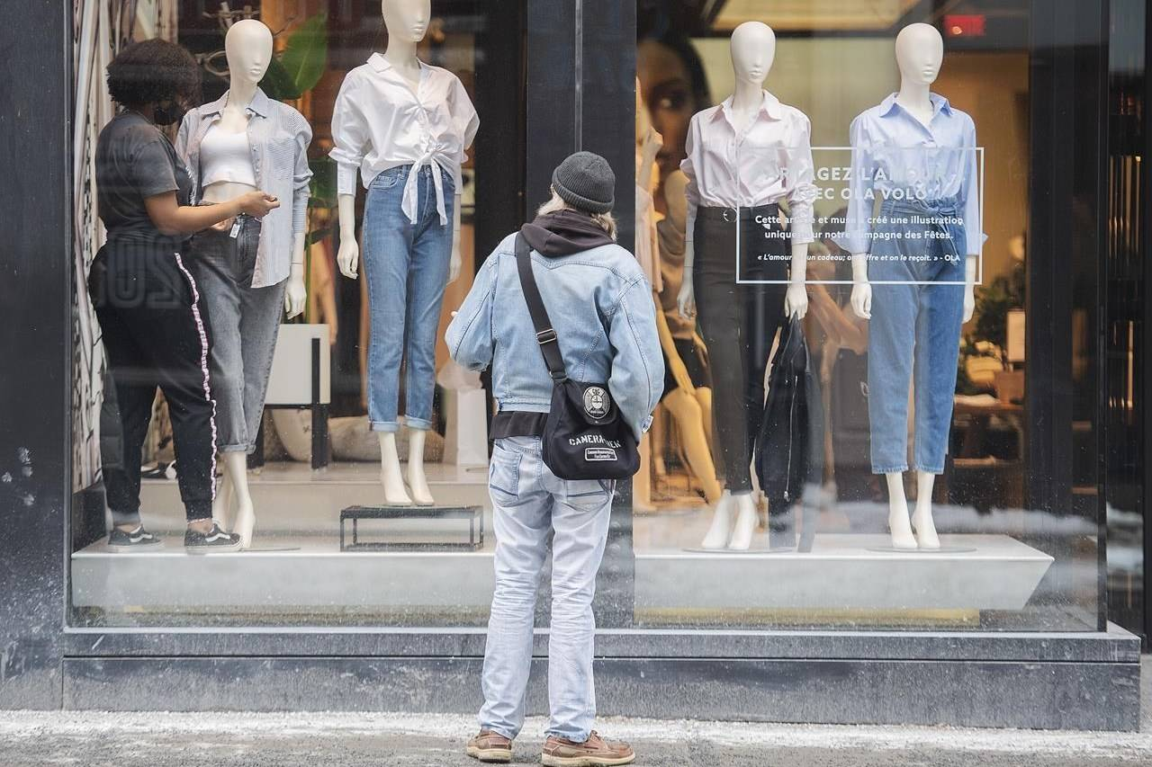 A woman dresses mannequins in a storefront window in Montreal, Sunday, Feb. 7, 2021, as the COVID-19 pandemic continues in Canada and around the world. THE CANADIAN PRESS/Graham Hughes
