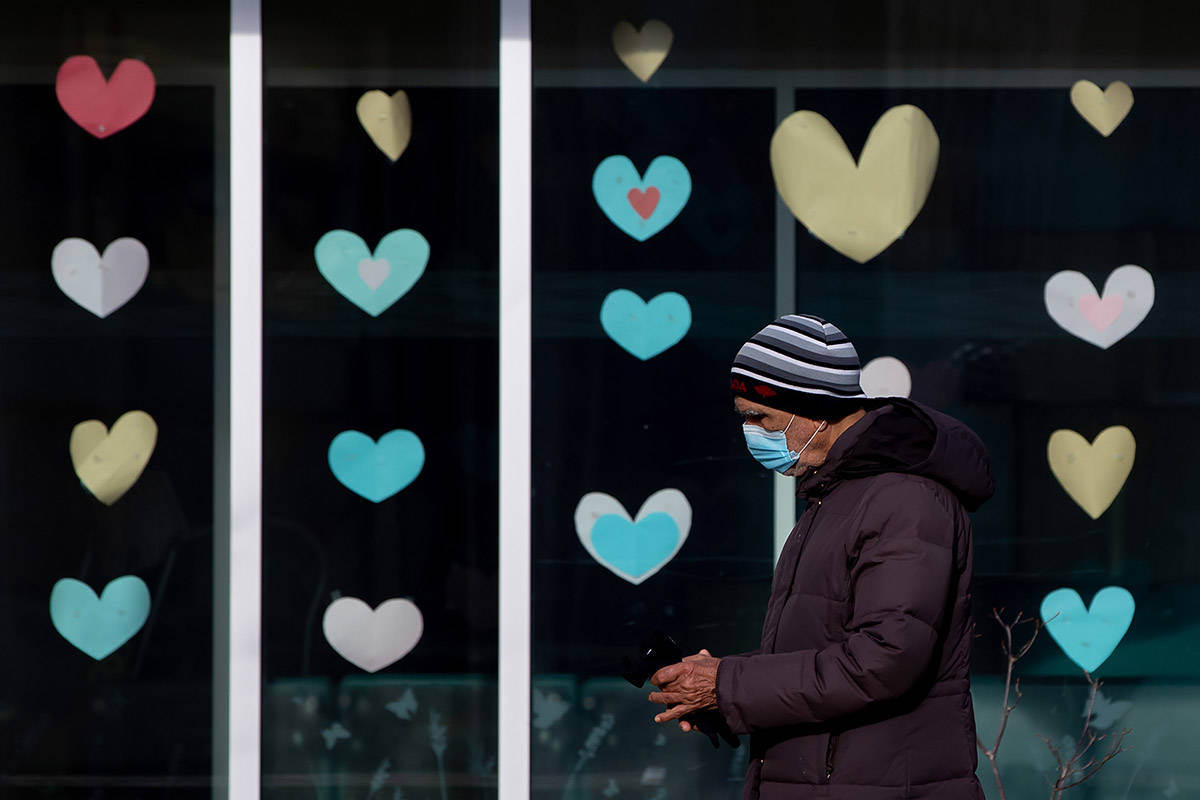 A man wearing a face mask to curb the spread of COVID-19 walks past paper hearts on the windows of a community centre, in Burnaby, B.C., on Sunday, February 7, 2021. THE CANADIAN PRESS/Darryl Dyck