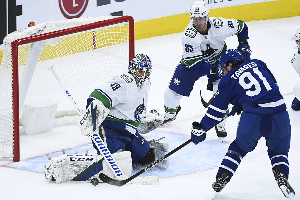 Vancouver Canucks goaltender Braden Holtby (49) stops Toronto Maple Leafs centre John Tavares (91) during third period NHL hockey action in Toronto on Monday, Feb. 8, 2021. THE CANADIAN PRESS/Nathan Denette
